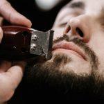 hombre-cierra-ojos-mientras-que-barbero-forma-su-barba-negra_1304-2778